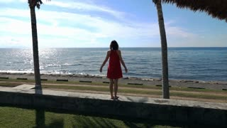 Young woman stretching her arms standing close to the sea, super slow motion