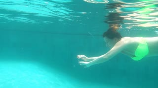 Young woman swimming under water, super slow motion