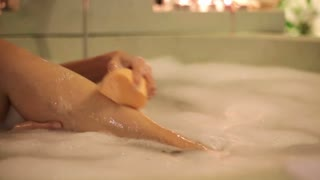 young woman taking bath in the bathroom at night, focus on legs