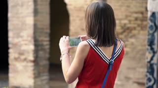 Young woman taking photo of ancient architecture in alcazar in Sevilla
