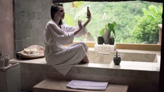 Young woman taking selfie with cellphone sitting on the edge of bathtub in bathroom