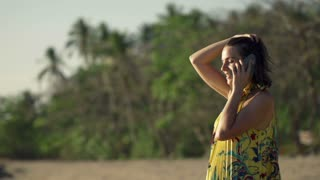 Young woman talking on cellphone on beautiful exotic beach