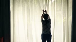 Young woman unveil curtains and looking on the garden, super slow motion