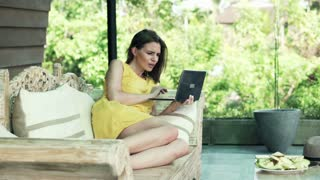 Young woman using modern laptop on wooden sofa on terrace