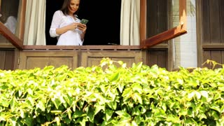 Young woman using smartphone on the window in country house