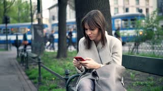 Young woman using smartphone sitting on bench in city park
