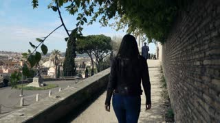 Young woman walking along the sidewalk in the city, super slow motion