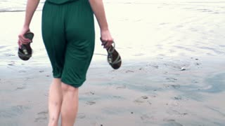 Young woman walking on the beach to the sea slow motion, shot at 240fps