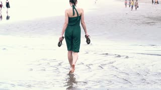Young woman walking on the beach to the sea super slow motion, shot at 240fps