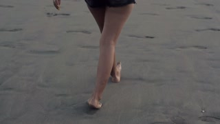Young woman walking on the beach to the sea