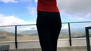 Young woman walking out on terrace and stretching her arms on terrace with mountain view, super slow motion