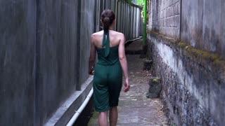 Young woman walking through narrow urban path