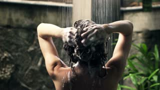 Young woman washing hair under shower in open bathroom