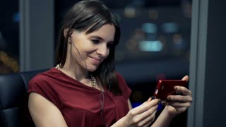 Young woman watching movie on smartphone at night