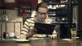 Young woman watching movie on tablet, by table at home at night