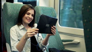 Young woman watching movie on tablet during train ride