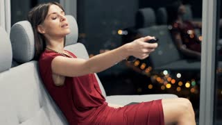 Young woman watching TV and drinking wine on sofa at night