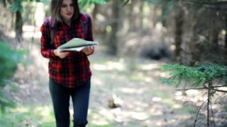 Young woman with a map looking for direction in forest