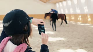Young, woman with helmet taking photo a man on horse during riding lesson