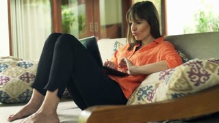 Young woman with laptop thinking about resolution on sofa in outdoor villa