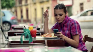 Young woman with smartphone eating salad in outdoor bar