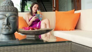 young woman with smartphone on luxury sofa at home