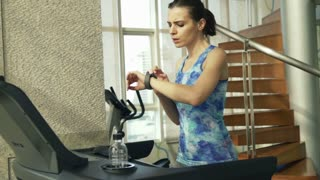 Young woman with smartwatch running on treadmill in gym, top view, shot at 240fps
