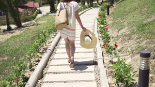 Young woman with summer hat walking in the park, slow motion 240fps