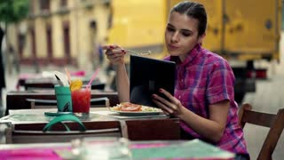 Young woman with tablet eating salad in outdoor bar
