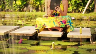 young woman sitting with tablet in the exotic, beautiful garden