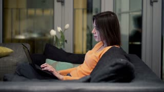 Young woman working on laptop sitting on sofa at home