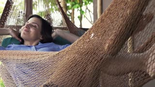 Young woman yawning and wake up after a nap on hammock on terrace, super slow motion, shot at 240fps