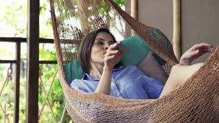 Young woman yawning and wake up after a nap on hammock on terrace