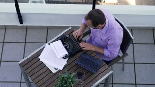 Young writer thinking, checking something on laptop while writing book on typewriter on terrace
