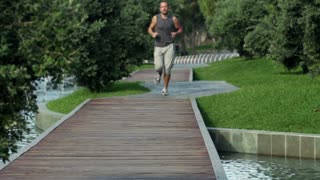 Young, attractive man jogging in city park slow motion, shot at 120fps