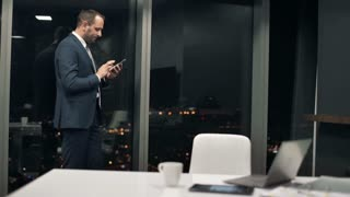 Young,happy businessman standing with smartphone by window during night in the office