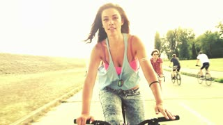 A beautiful and attractive girl sending kisses to the camera while having fun cycling with her friends, graded warmer, in slow motion.