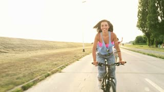 A beautiful and attractive girl sending kisses to the camera while having fun cycling with her friends, graded warmer.