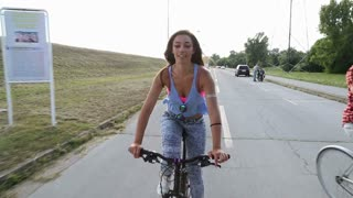 A beautiful and attractive girl sending kisses to the camera while having fun cycling with her friends, in slow motion.