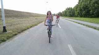 A beautiful and attractive girl sending kisses to the camera while having fun cycling with her friends.