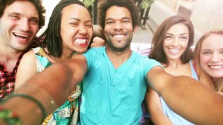 A close up of a group of five friends having fun taking a group selfie, graded brighter.