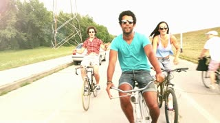 A wide shot of a group of young adults while they are cycling outdoors and having a great time, graded warmer