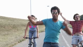 A wide shot of a group of young adults while they are cycling outdoors and having a great time, in slow motion.
