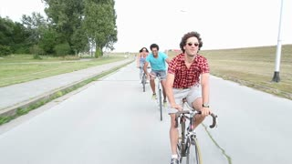 A wide shot of a group of young adults while they are cycling outdoors and having a great time.