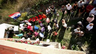 Aerial view of bride and groom followed by guests and band in backyard on wedding day
