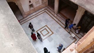 Aerial view of people passing through hall of building in Mehrangarh fort.