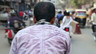 AGRA, INDIA - 26 FEBRUARY 2015: Back seat view of man riding bicycle through busy street in Agra, closeup.