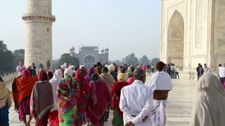 AGRA, INDIA - 26 FEBRUARY 2015: Tourists walking down the front patio of Taj Mahal.
