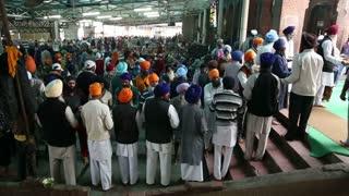 AMRITSAR, INDIA - 1 MARCH 2015: Crowd of people sharing food at Guru Ka Langar, public kitchen in Amritsar.