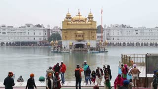 AMRITSAR, INDIA - 1 MARCH 2015: Golden temple in Amritsar, with water in front people standing at dock.
